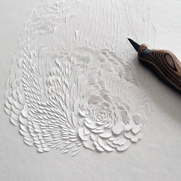 Large, abstract paper cut art of wings, feathers and flowers.
